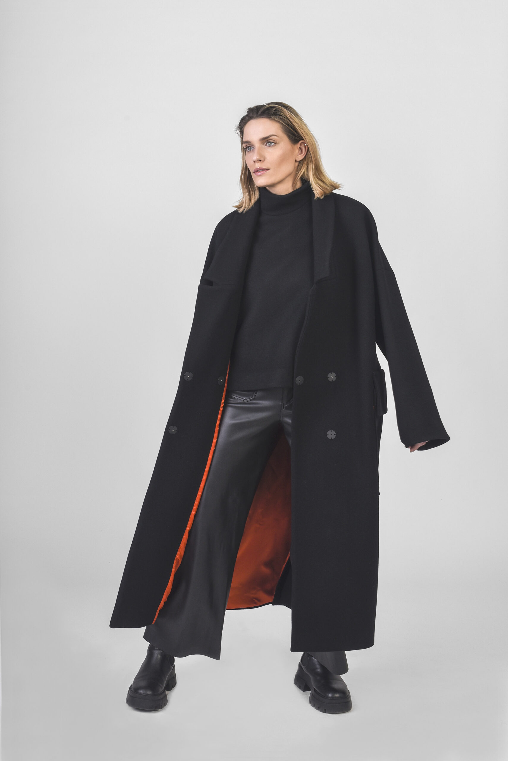 model with black coat and orange linen